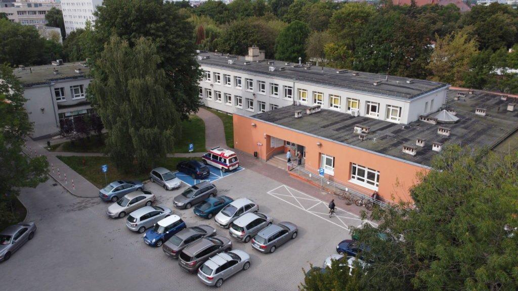 Budynek przychodni i parking, na którym zaparkowano samochody. - grafika artykułu