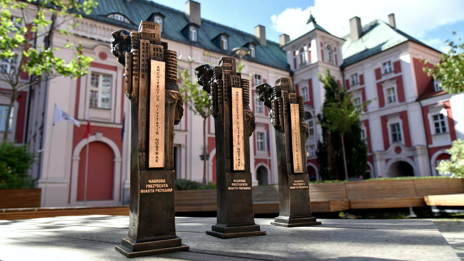 Na pierwszym planie statuetki w konkursie Architectus civitatis nostrae, na drugim urząd miasta. - grafika artykułu