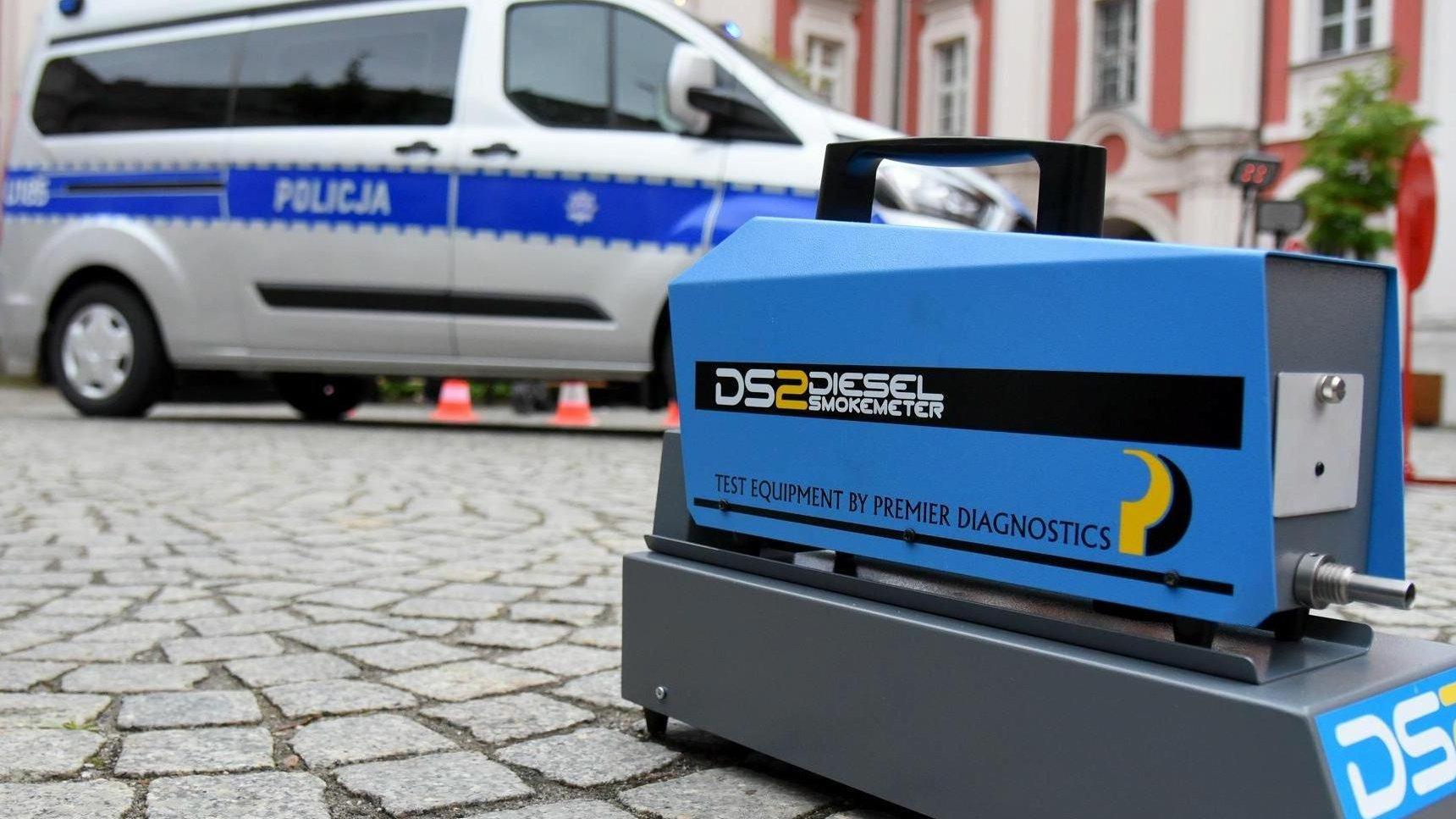 Na pierwszym planie znajduje się urządzenie do pomiaru spalin. W tle widać policyjny samochód oraz urząd miasta. - grafika artykułu