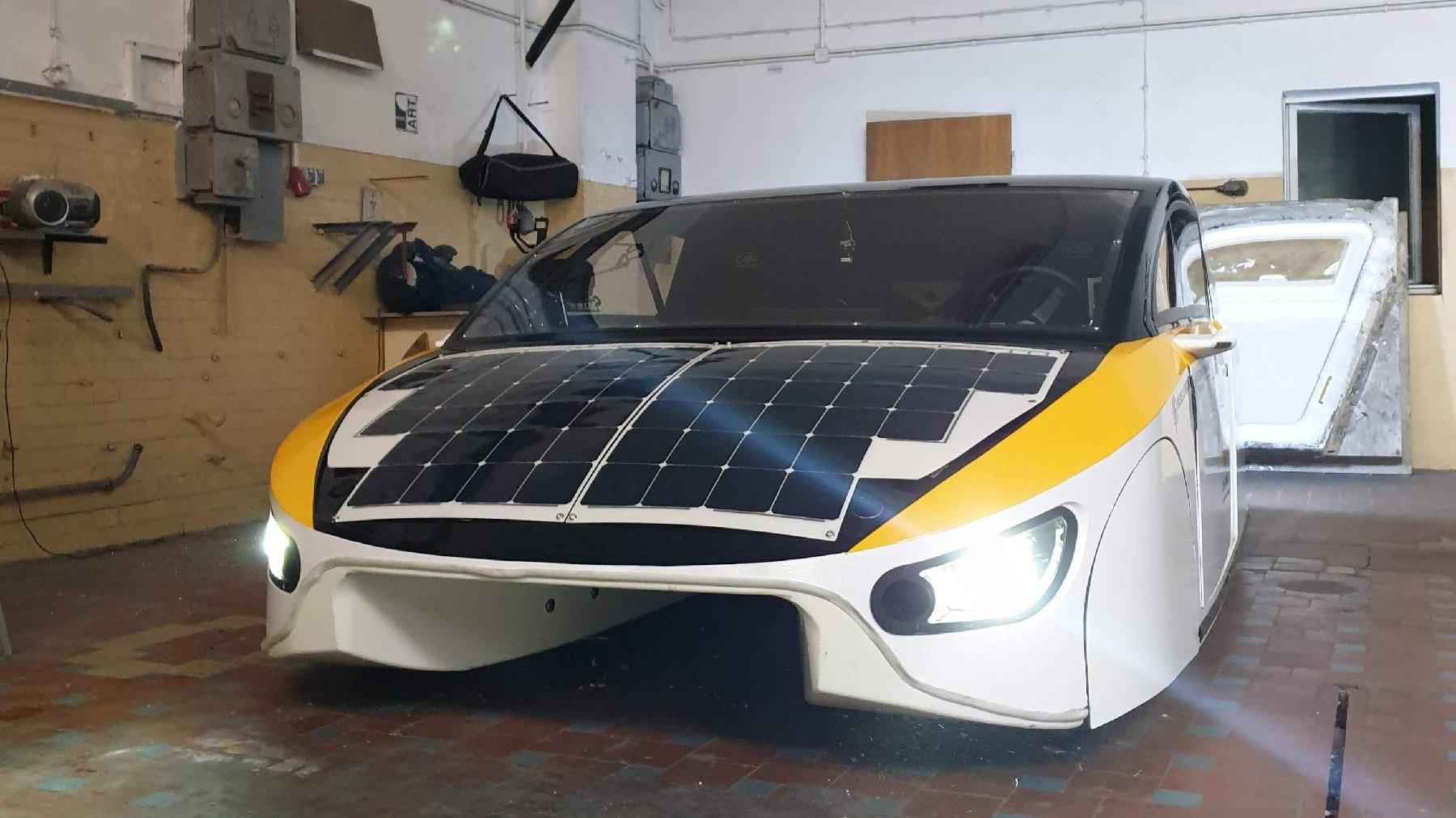 Na zdjęciu samochód z panelalmi fotowoltaicznymi zaparkowany w garażu. - grafika artykułu