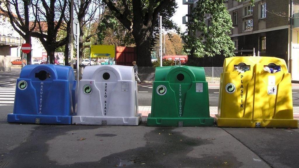 Na zdjęciu znajdują się cztery kolorowe pojemniki na odpady (niebieski, biały, zielony i żółty) stojące na chodniku, przy ulicy. - grafika artykułu