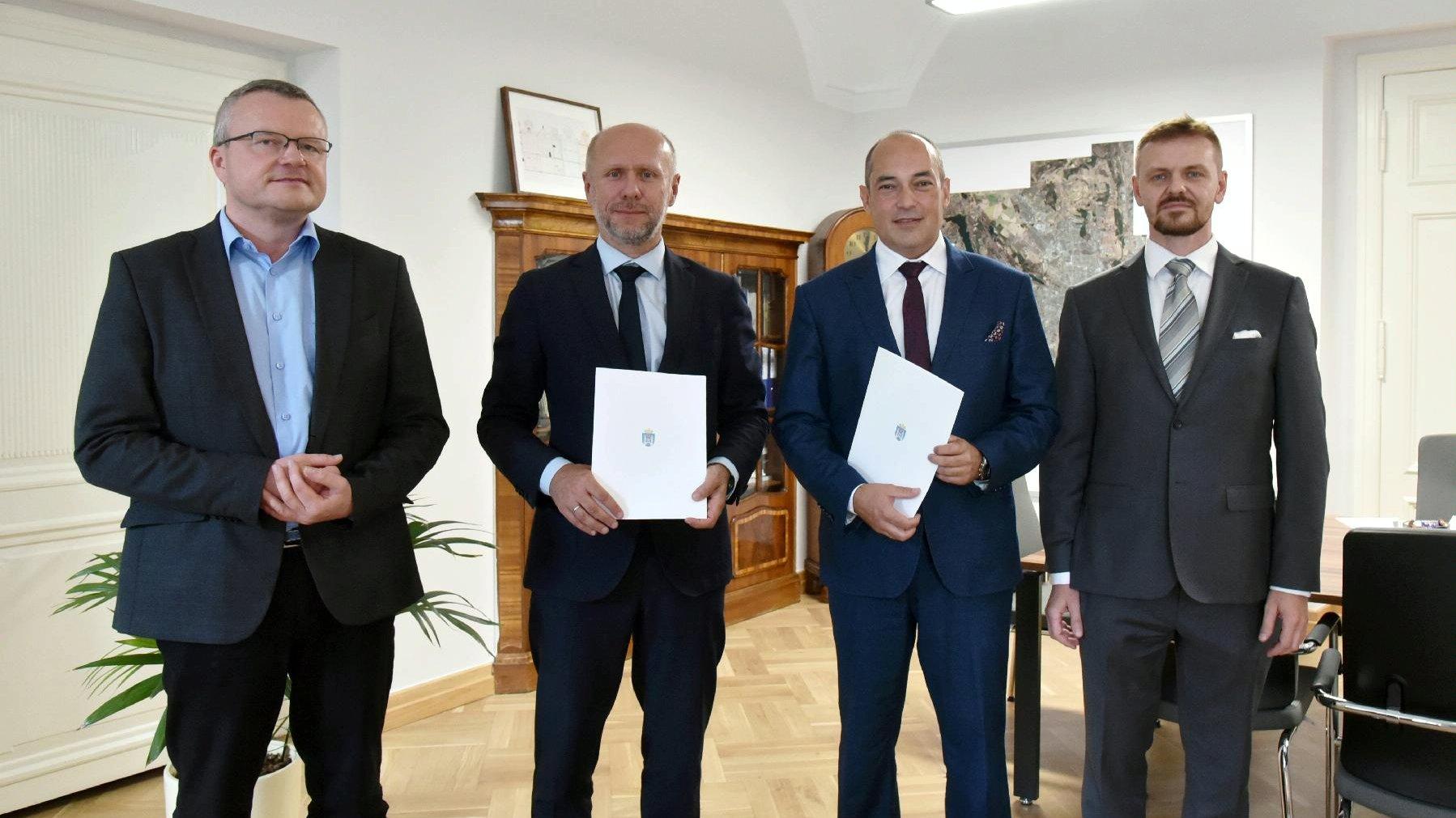 Na zdjęciu znajdują się wiceprezydent Poznania - Bartosz Guss, Marcin Kraska - wiceprezes Centrum Łukasiewicz oraz jego asystent i miejski energetyk. Wiceprezes i wiceprezydent trzymają w rękach teczkę z porozumieniem. - grafika artykułu