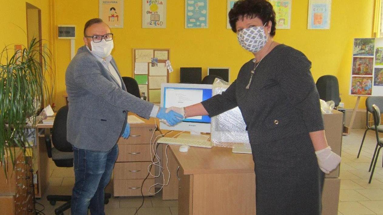 Na zdjęciu znajduje się darczyńca oraz dyrektorka szkoły, którzy podają sobie ręce. Na biurkach stoją komputery, na ścianie wiszą obrazki namalowane przez dzieci. - grafika artykułu