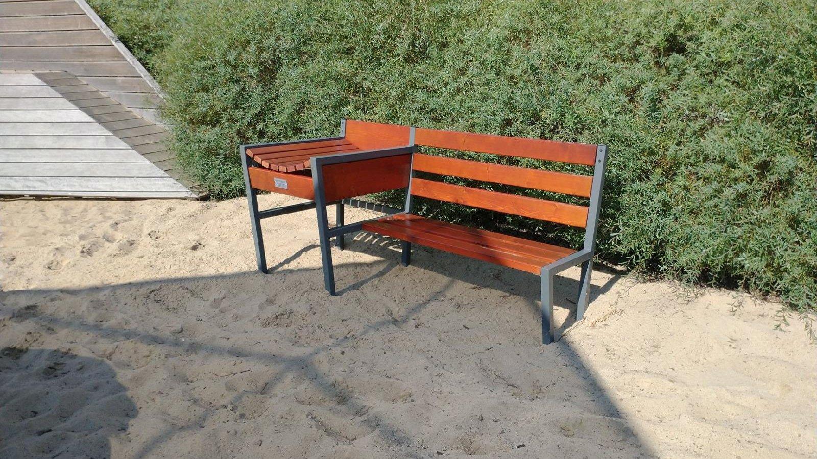 Na zdjęciu znajduje się ławka z zamontowanym przewijakiem dla dzieci. Ławka stoi na piasku, w tle widać zielone krzewy. - grafika artykułu