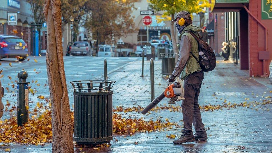 Na zdjęciu znajduje się mężczyzna z dmuchawą do liści. Człowiek ten stoi na chodniku, obok znajduje się ulica. Na fotografii widać także takie elementy jak kosze na śmieci czy zaparkowane samochody. - grafika artykułu
