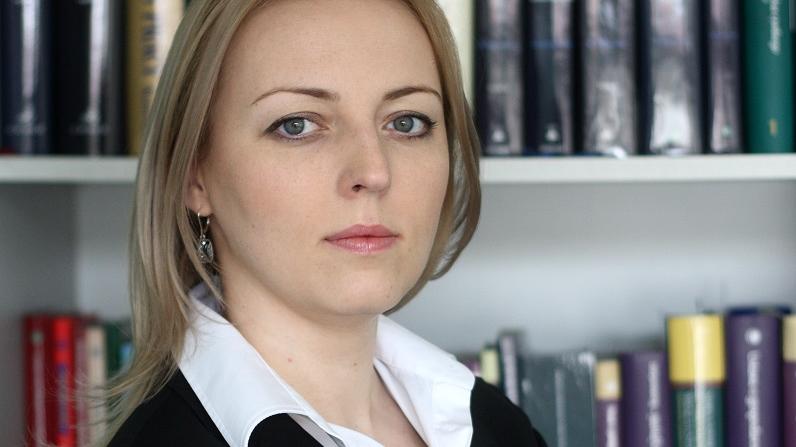 Natalia Weremczuk stoi z założonymi rękami na tle regału z książkami - grafika artykułu