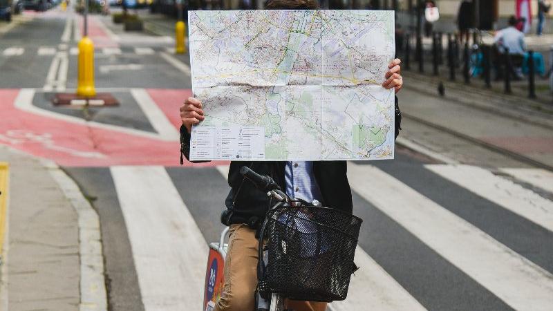 Mężczyzna na rowerze w centrum miasta, w rękach trzyma mapę - grafika artykułu
