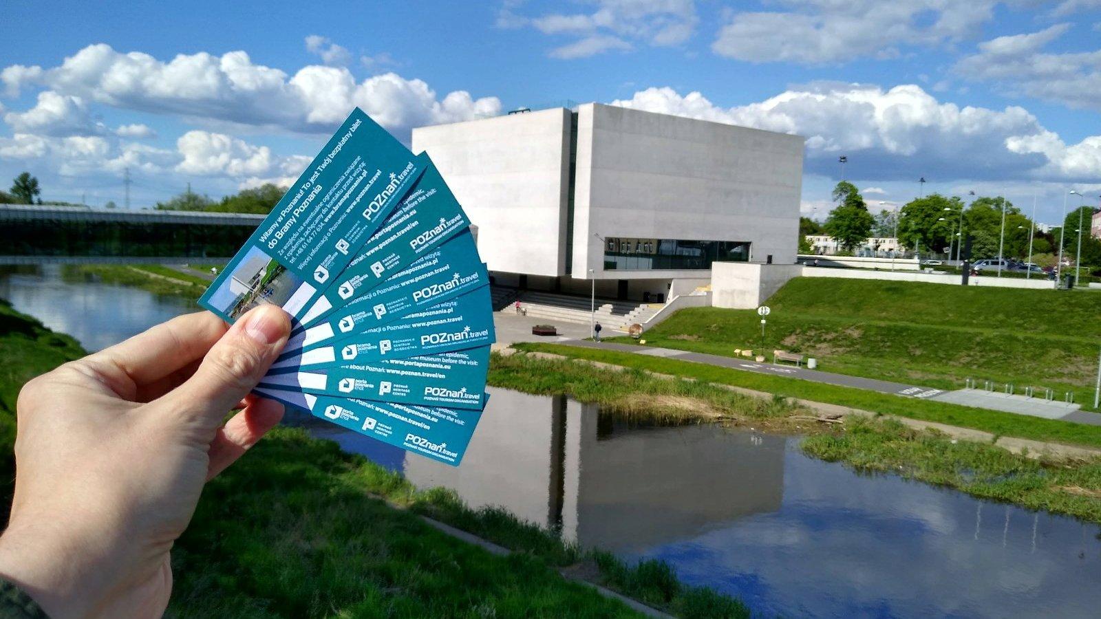 Zdjęcie przedstawia rękę trzymającą bilety. W tle widać budynek Bramy Poznania. - grafika artykułu