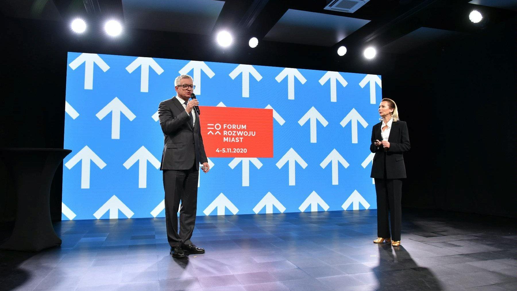 Prezydent Poznania Jacek Jaśkowiak mówi do mikrofonu, na przeciwko stoi Iwona Matuszczak - Szulc, dyrektorka Wydziału Rozwoju Miasta i Współpracy Międzynarodowej UMP. - grafika artykułu