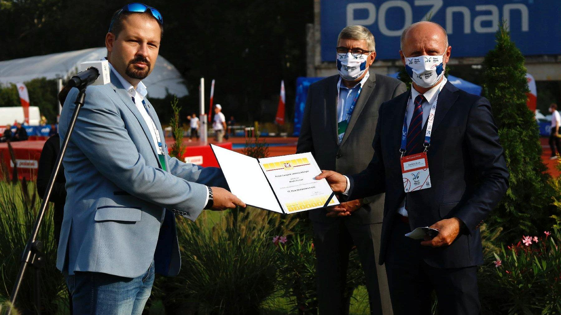 Przedstawiciel PZLA wręcza Bartoszowi Gussowi certyfikat przyznania Poznaniowi organizację Mistrzostw Polski w lekkoatletyce w 2021. Na drugim planie Grzegorz Ganowicz, przewodniczący Rady Miasta - grafika artykułu