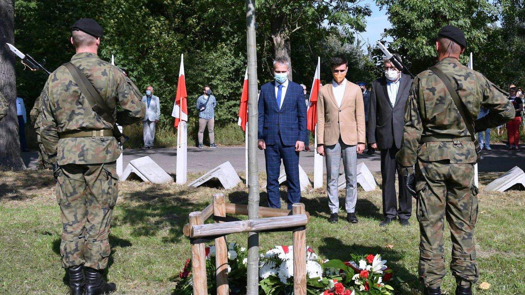 Przedstawiciele Miasta (zastępca prezydenta Jędrzej Solarski i miejscy radni) składają kwiaty pod dębem pamięci. - grafika artykułu