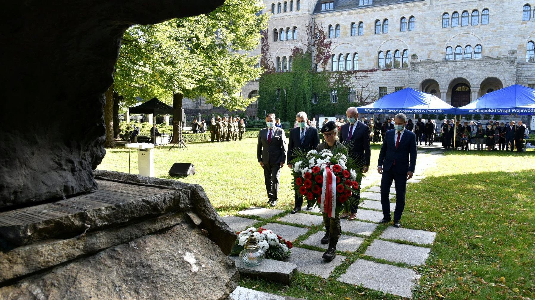 Przedstawiciele władz miasta i województwa składają kwiaty pod pomnikiem Ofiar Katynia i Sybiru. - grafika artykułu
