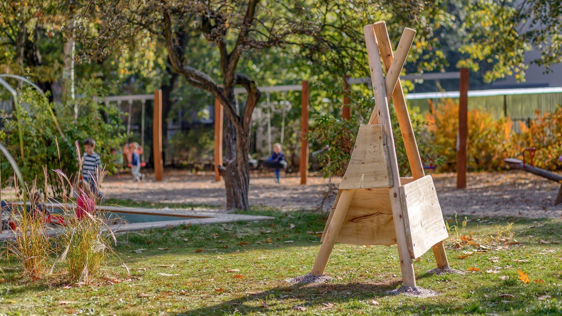 Przedszkolny plac zabaw. Na zdjęciu widać stację meteorologiczną - drewnianą konstrukcja przypominająca indiańskie tipi. W tle znajdują się dzieci. - grafika artykułu