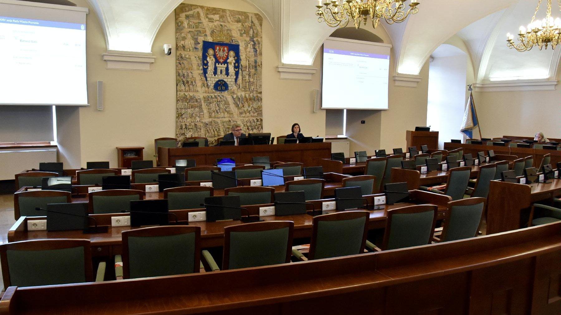 Sala sesyjna. Krzesła radnych są puste, na swoim miejscu siedzi tylko Grzegorz Ganowicz, przewodniczący rady oraz jego zastępczyni - grafika artykułu
