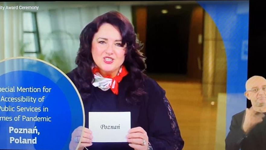 Screen: komisarz Helena Dali trzyma kartkę z nazwą zwycięskiego miasta: Poznań. Obok - tłumacz języka migowego - grafika artykułu