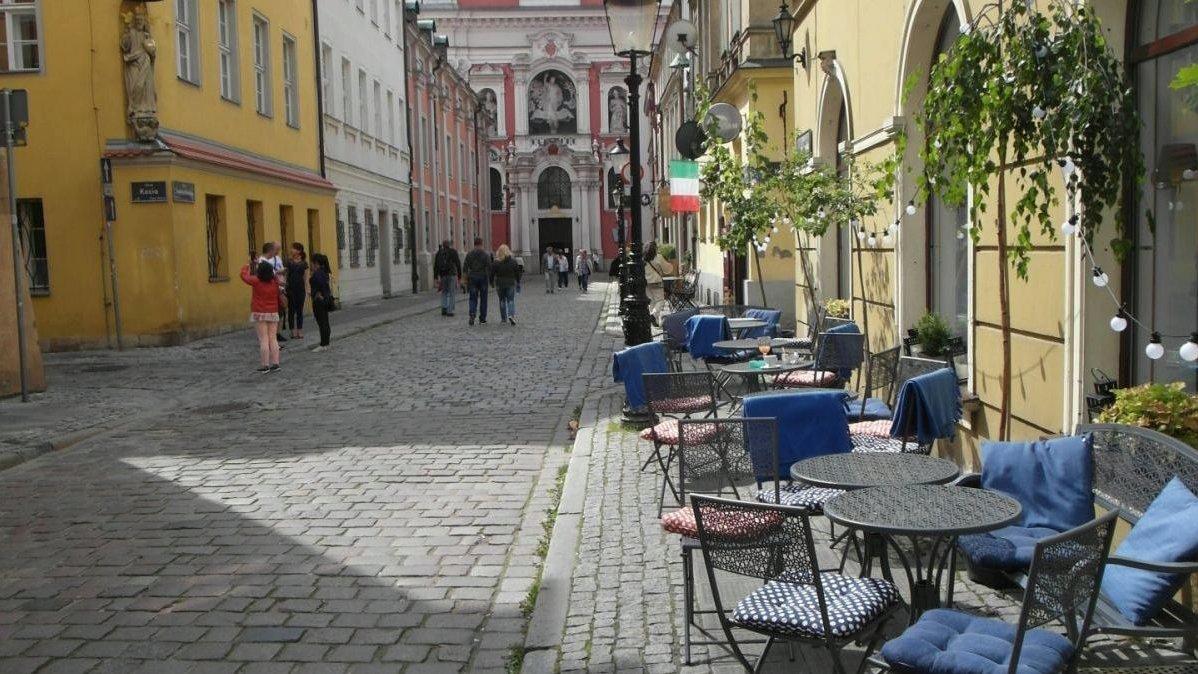 Zdjęcie: na pierwszym planie ogródek gastronomiczny, na krzesłach wiszą niebieskie koce. W tle poznańska fara - grafika artykułu
