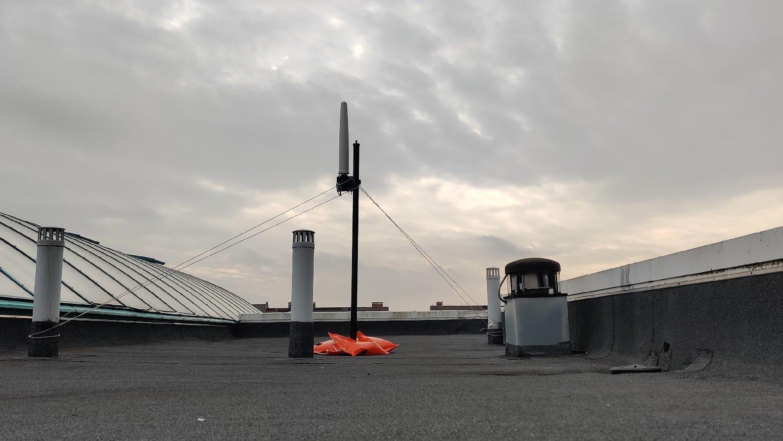 Zdjęcie przedstawia aparaturę do badania pól elektromagnetycznych umieszczoną na dachu budynku. - grafika artykułu