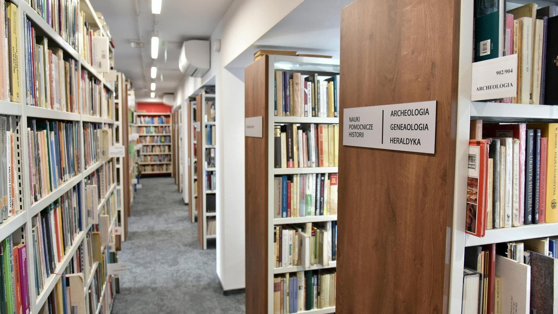 Zdjęcie przedstawia biblioteczne półki z książkami. - grafika artykułu
