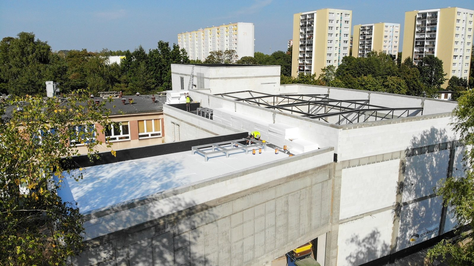 Zdjęcie przedstawia budynek szkoły w trakcie rozbudowy, widziany z góry. W tle znajdują się bloki. - grafika artykułu