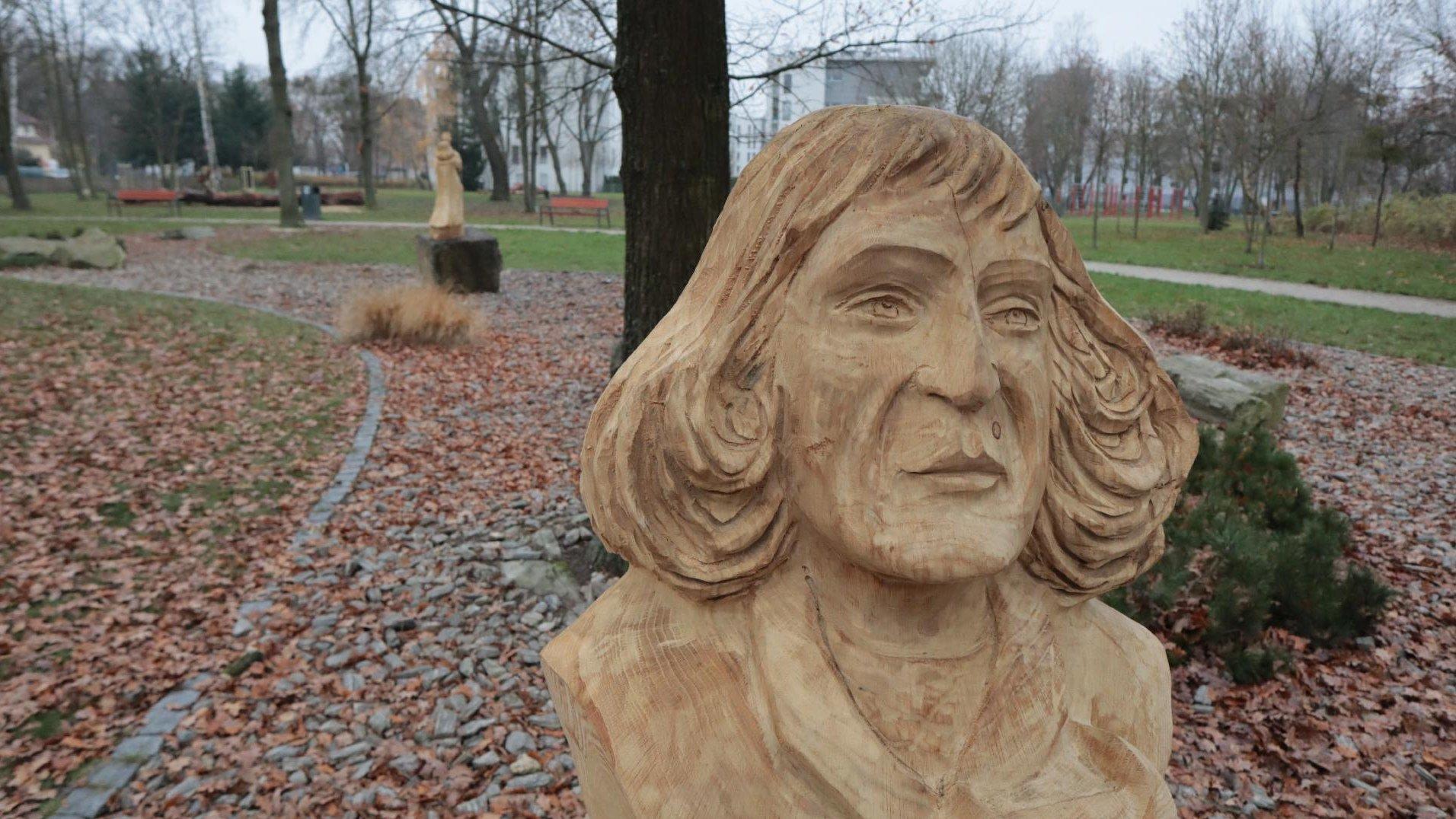 Zdjęcie przedstawia drewnianą rzeźbę Mikołaja Kopernika. W tle widać park oraz inną drewniana rzeźbę. - grafika artykułu
