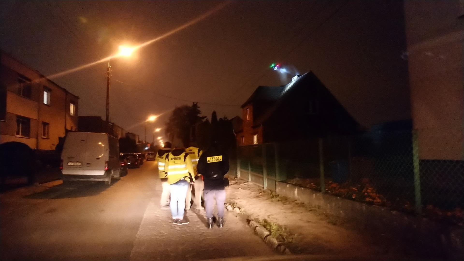 Zdjęcie przedstawia drona, latającego nad budynkami po zmroku. Na chodniku stoją osoby obsługujące drona w odblaskowych kamizelkach i strażnicy miejscy. - grafika artykułu