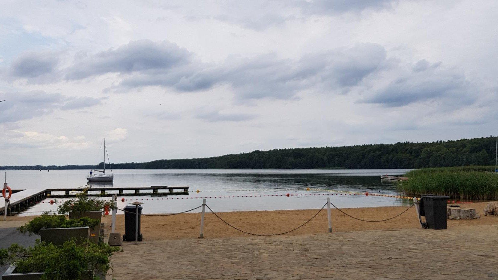 Zdjęcie przedstawia miejską plażę. Na jeziorze widać pomost i statek. - grafika artykułu