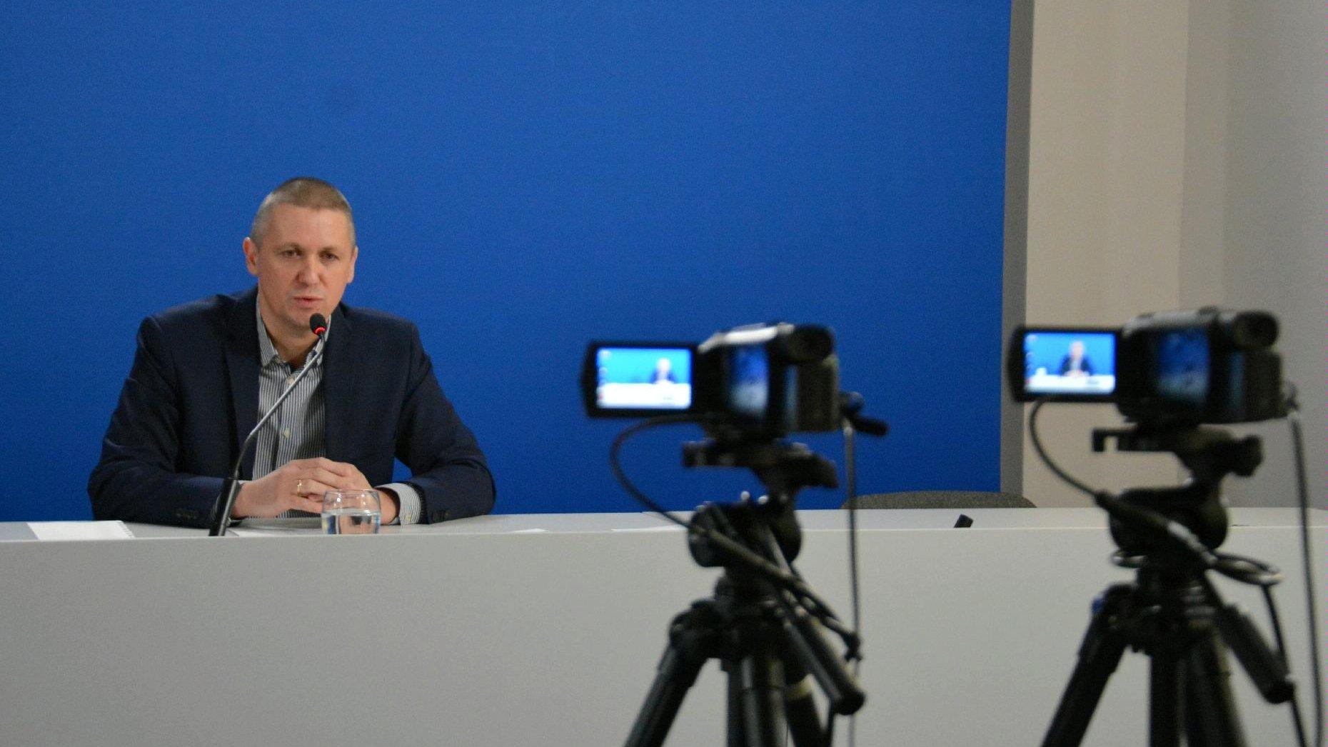 Zdjęcie przedstawia Patryka Pawełczaka, dyrektora Gabinetu Prezydenta UMP. Dyrektor siedzi za biurkiem, na pierwszym planie widać kamery. - grafika artykułu