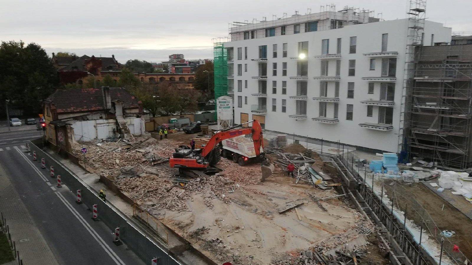 Zdjęcie przedstawia plac budowy. Widać na nim koparkę i pracowników budowlanych. - grafika artykułu