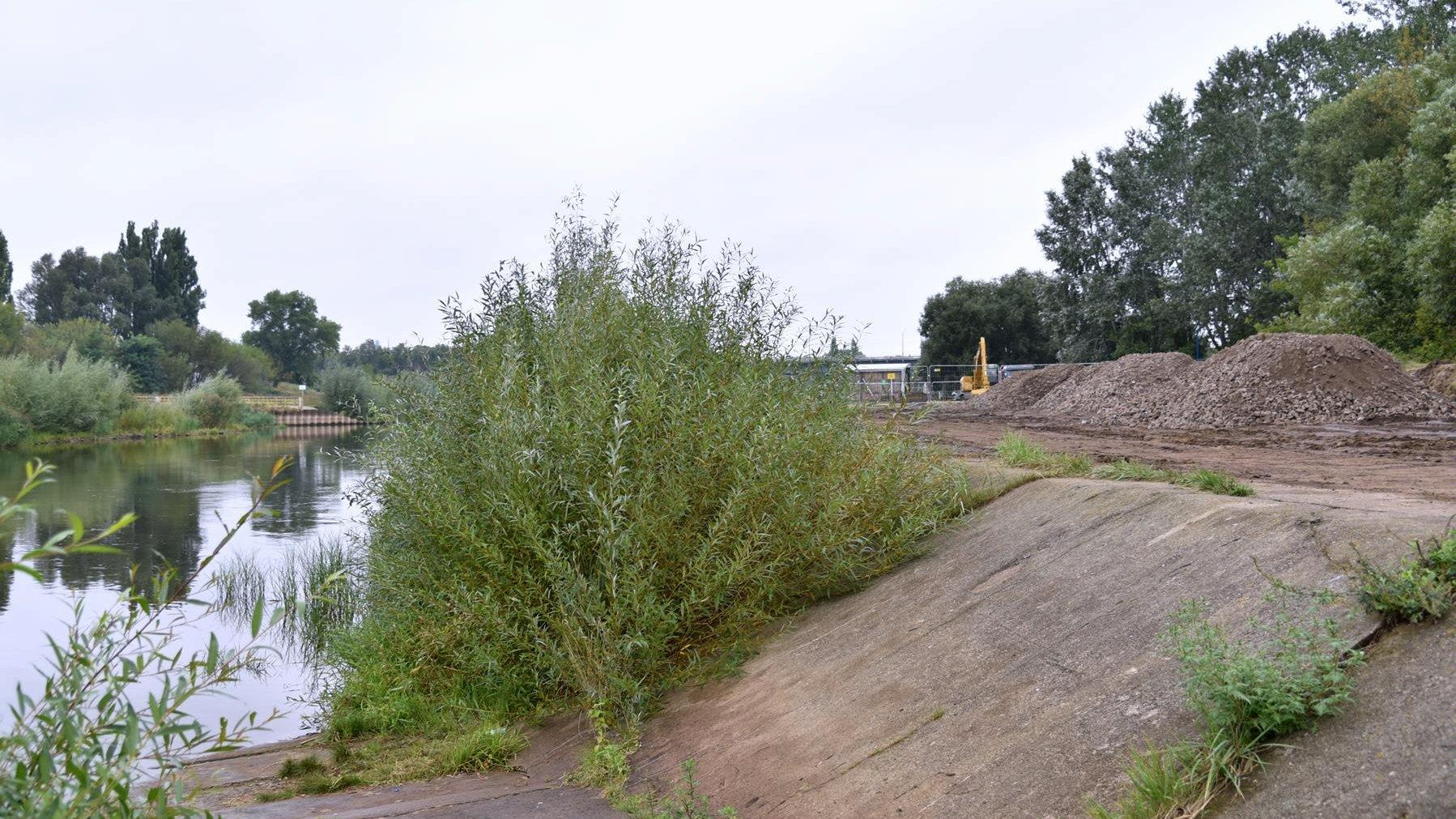 Zdjęcie przedstawia początek prac budowlanych. Po jednej stronie widać rzekę, po drugiej hałdy ziemi - grafika artykułu