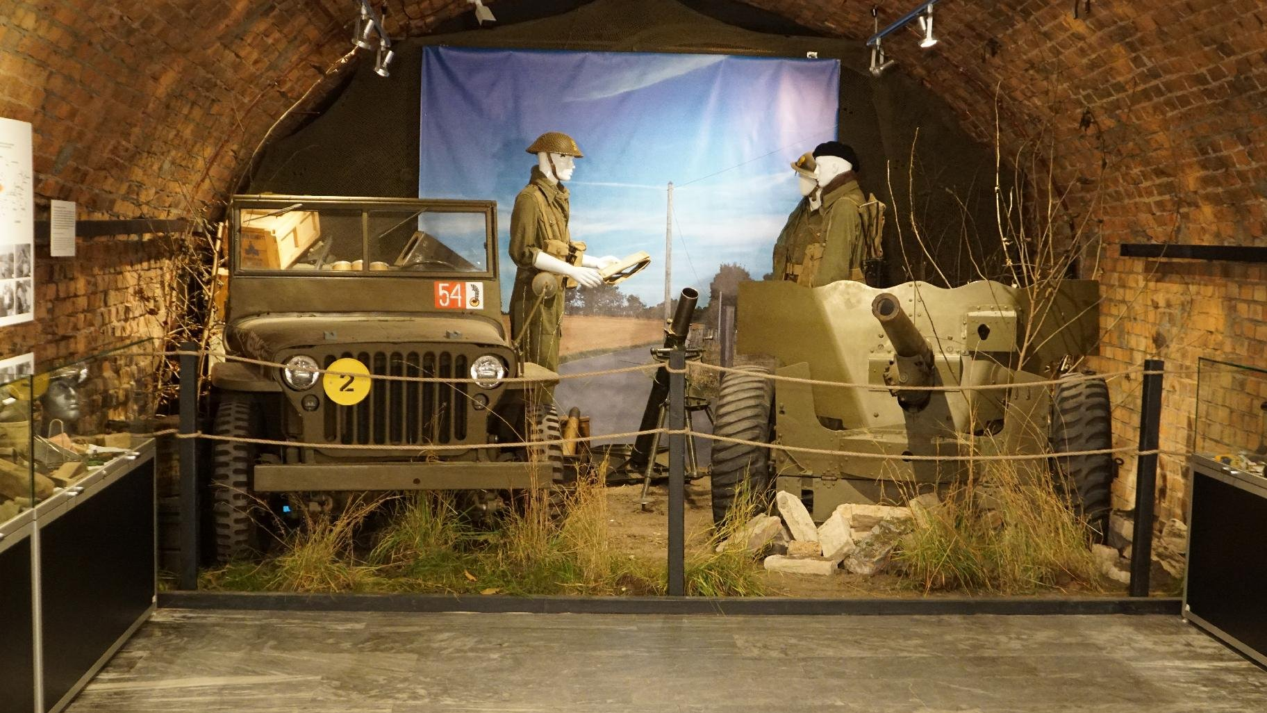 Zdjęcie przedstawia samochód wojskowy i działo. Na drugim planie manekiny ubrane w mudury. - grafika artykułu