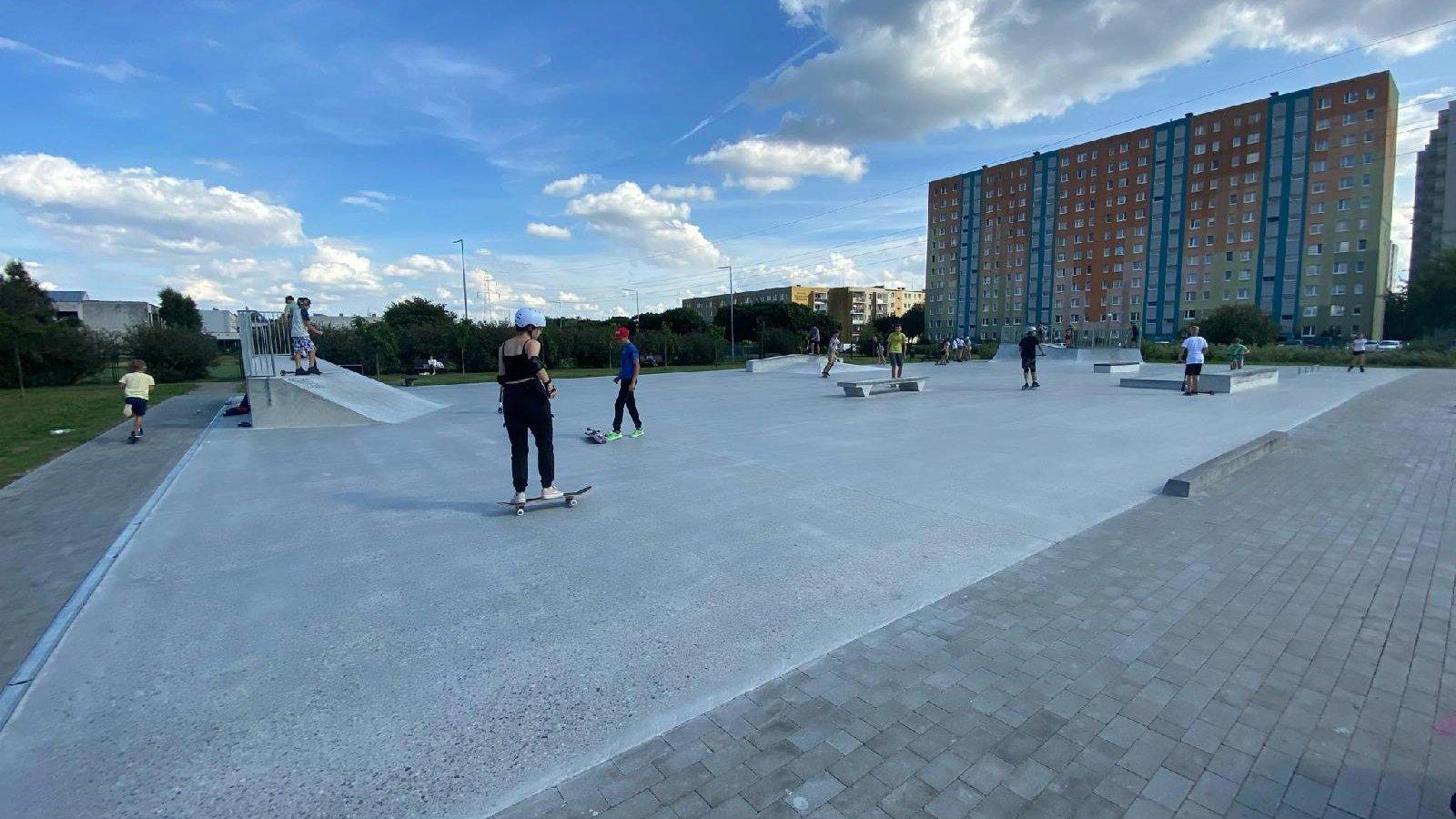 Zdjęcie przedstawia skatepark. Widać na nim młode osoby jeżdżące na deskorolkach, w tle znajdują się bloki - grafika artykułu