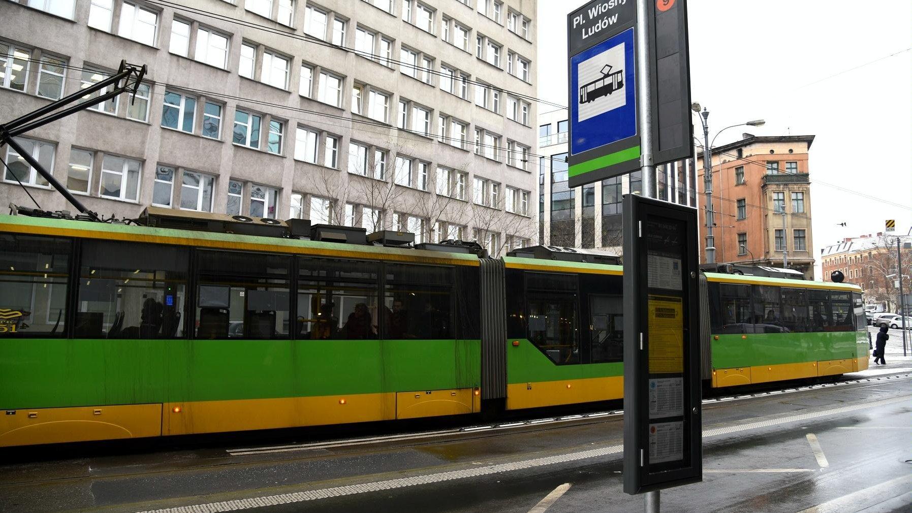 Zdjęcie przedstawia słup przystankowy przy ul. Strzeleckiej (nazwa przystanku to Pl. Wiosny Ludów). W tle widać tramwaj, ulicę i budynki. - grafika artykułu
