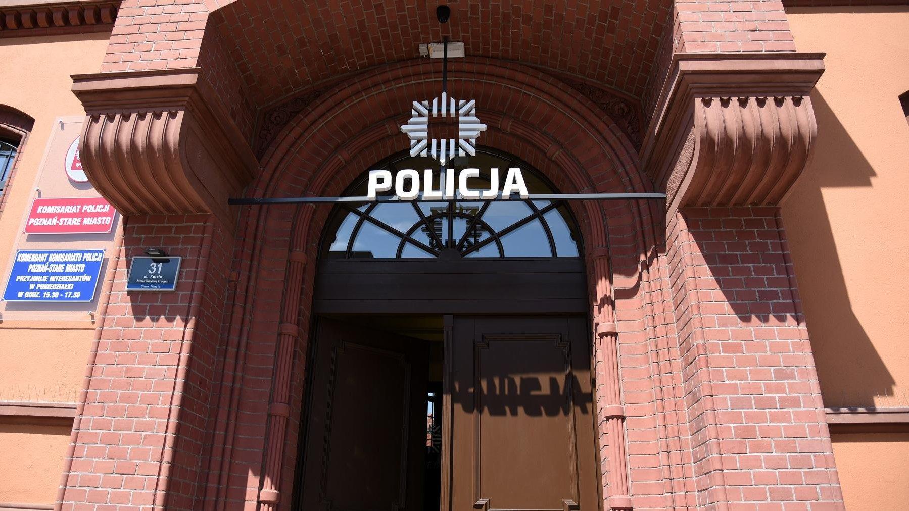 """Zdjęcie przedstawia wejście na komisariat policji. Duże drewniane drzwi, nad nimi biały napis """"policja"""" oraz znak tej służby mundurowej - grafika artykułu"""