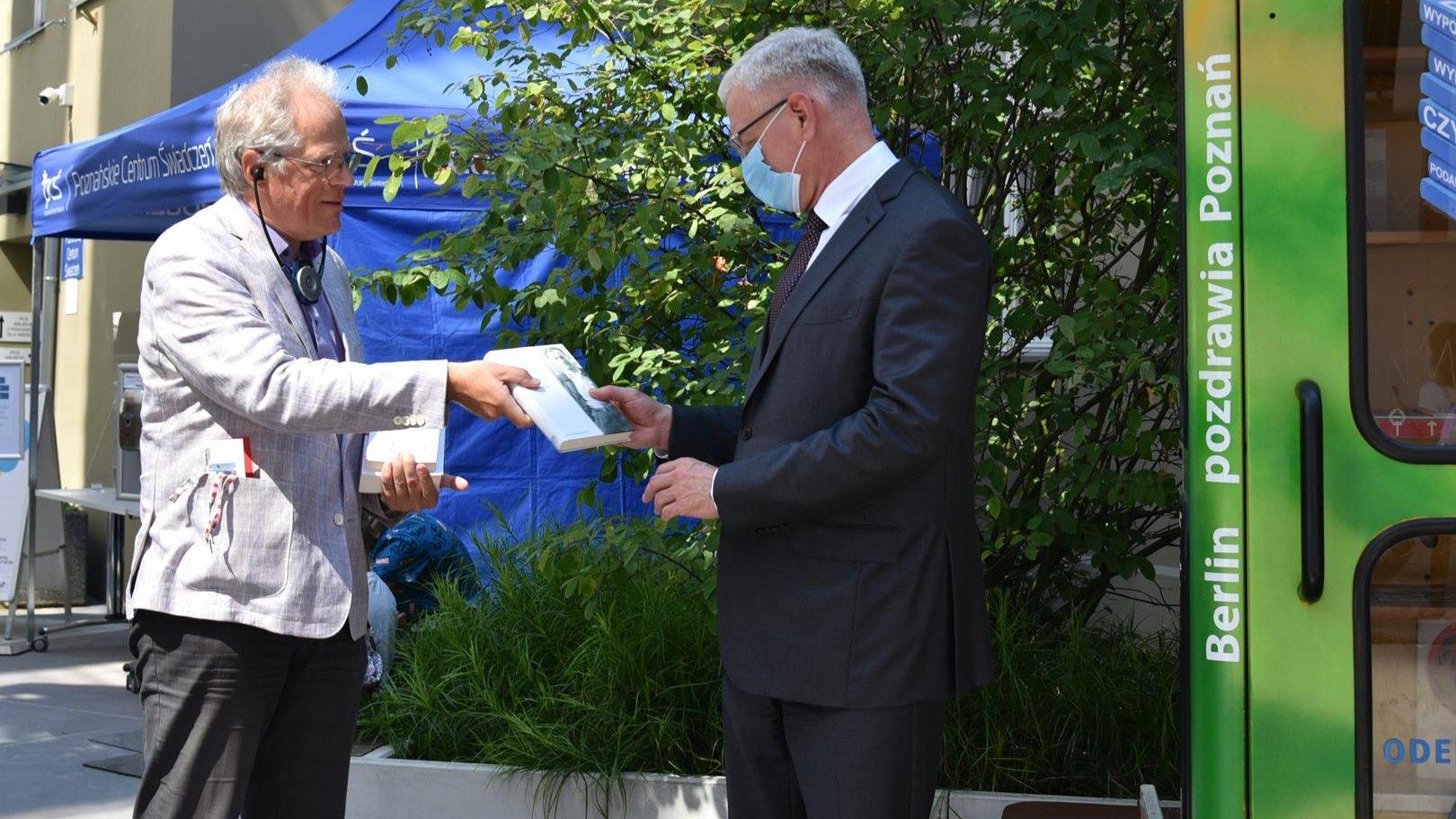 Jacek Jaśkowiak, prezydent Poznania, odbiera przed Biblioboxx książkę od Heinera Klempa, przedstawiciela Landtagu