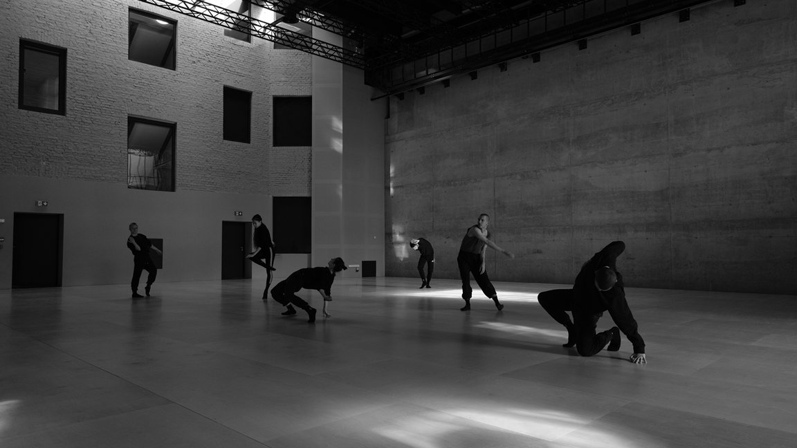 Black and white photo of dancers in various poses in empty, modern space. - grafika artykułu